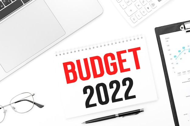 Tekst budżet 2022 na karcie. laptop, okulary, długopis, kalkulator i schowek z wykresami i wykresami. plan biznesowy. widok z góry.
