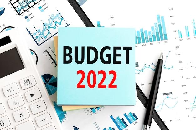 Tekst budżet 2022 na naklejkach. pióro i kalkulator w schowku z wykresami, dokumentami i wykresami. plan biznesowy. widok z góry.
