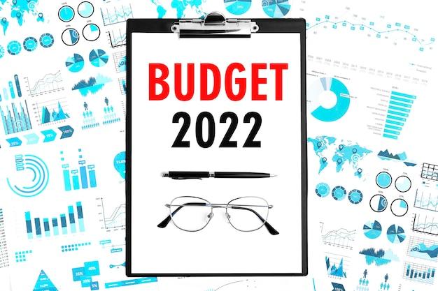 Tekst budżet 2022 w schowku. pióro i okulary w schowku z wykresami, dokumentami i wykresami. widok z góry koncepcja biznesowa.