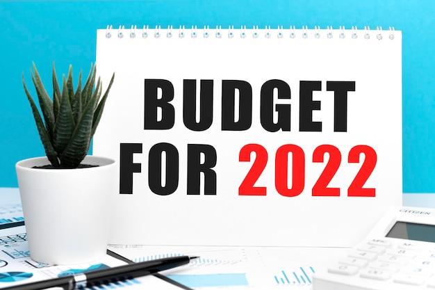 Tekst budżet na 2022 r. na karcie. pióro i kalkulator w schowku z wykresami, dokumentami i wykresami. plan biznesowy. widok z góry.