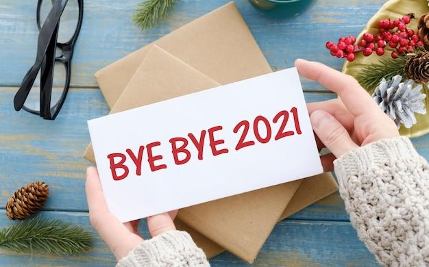 Tekst bye bye 2021 na białym papierze na czerwonym tle bożego narodzenia. koncepcja pożegnania z 2021 r.
