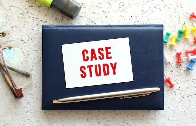 Tekst case study na wizytówce leżącej na niebieskim notesie obok okularów i papeterii. pomysł na biznes.