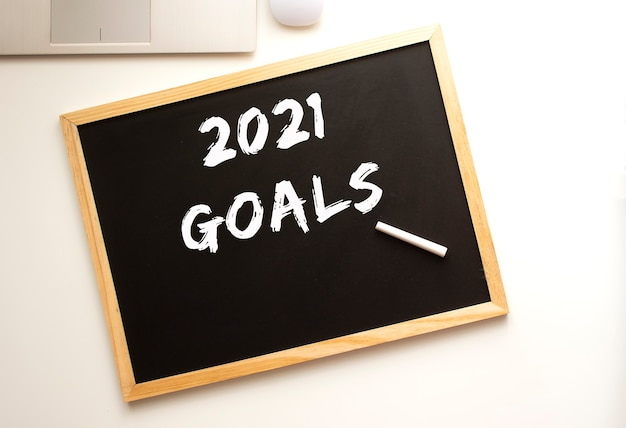 Tekst cele 2021 napisane kredą na tablicy łupkowej. biurko. pomysł na biznes.