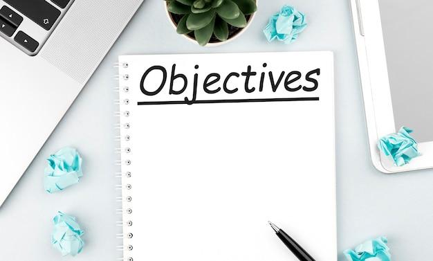 Tekst cele w notatniku. laptop, kawałki papieru, długopis i roślina na biurku. płaski świeckich, widok z góry. koncepcja planowania.