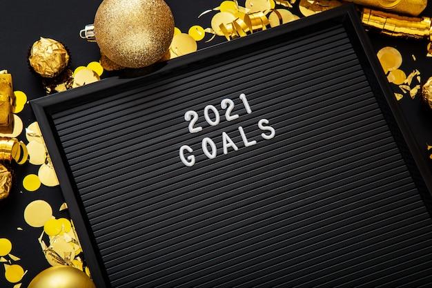 Tekst celów na rok 2021 na czarnej tablicy z listami w świątecznym wystroju