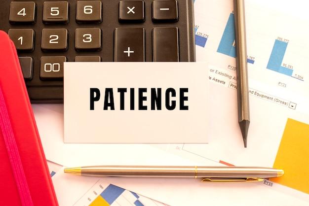 Tekst cierpliwość na białej karcie z metalowym długopisem, kalkulatorem i wykresami finansowymi