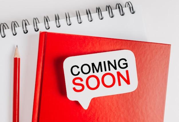 Tekst coming soon na białej naklejce na czerwonym notatniku z tłem biurowym. mieszkanie leżało na koncepcji biznesu, finansów i rozwoju