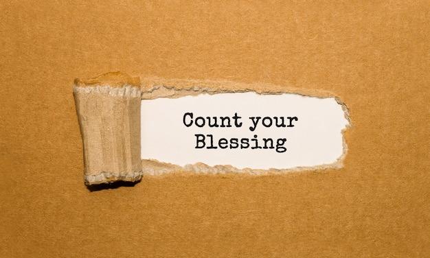 Tekst count your blessing znajdujący się za podartym brązowym papierem