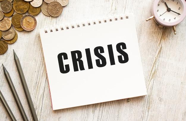 Tekst crisis na kartce notatnika. monety rozrzucone, ołówki na szarej drewnianej powierzchni