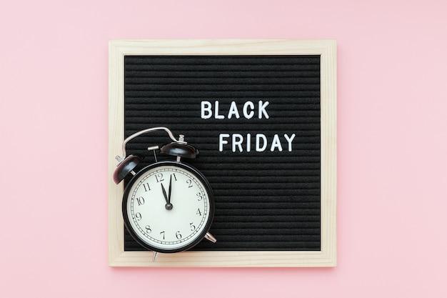 Tekst czarny piątek na czarnej tablicy i budzik na różowym tle. koncepcja czarny piątek, czas sprzedaży w sezonie