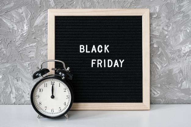 Tekst czarny piątek na czarnej tablicy i budzik na stole