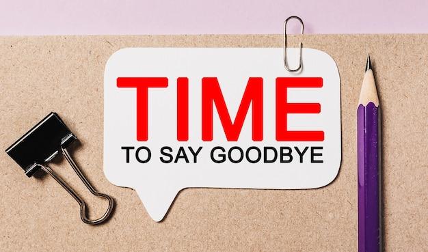 Tekst czas na pożegnanie na białej naklejce z powierzchnią biurową