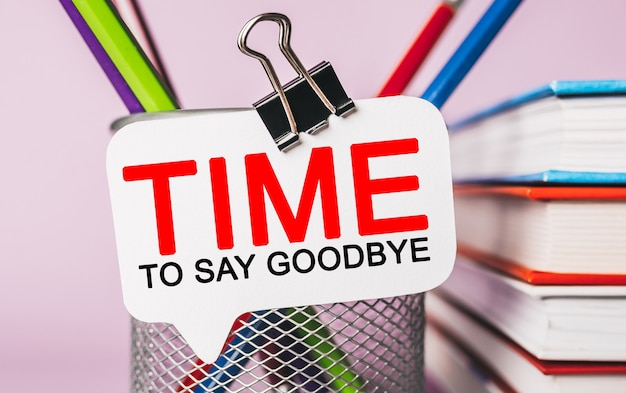 Tekst czas na pożegnanie na białej naklejce z tłem papeterii biurowej. mieszkanie leżało na koncepcji biznesu, finansów i rozwoju