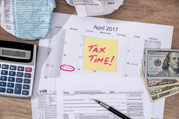 """Tekst """"czas podatkowy"""" na formularzach podatkowych 1040 z piórem, kalkulatorem i pieniędzmi."""