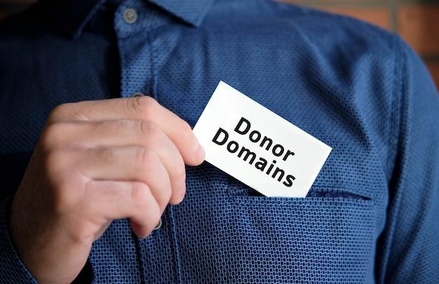 Tekst domeny dawcy na białym znaku w dłoni mężczyzny w koszuli