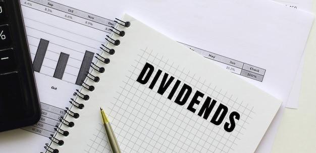 Tekst dywidendy na stronie notatnika leżącego na wykresach finansowych na biurku