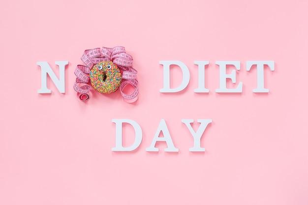 Tekst dzień bez diety i abstrakcyjna śmieszna twarz kobiety z pączka z oczami i włosami z centymetrowej taśmy na talerzu