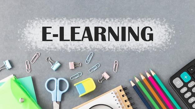 Tekst e-learningowy napisany na ciemnym tle, w pobliżu przyborów szkolnych.
