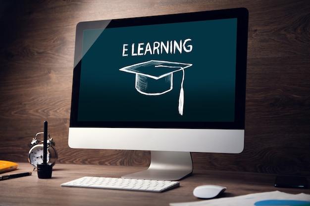 """Tekst """"e learningu"""" na ekranie komputera ze stołem roboczym"""
