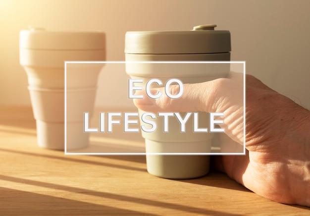 Tekst ekologicznego stylu życia nad zdjęciem z kubkami wielokrotnego użytku.