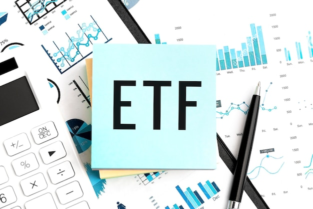 Tekst etf exchange traded fund na niebieskiej naklejce, kalkulatorze, długopisie, wykresach. biznesowe mieszkanie leżało.