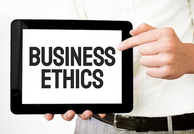 Tekst etyka biznesowa na białym talerzu papierowym w rękach biznesmena na białym bakcground. pomysł na biznes