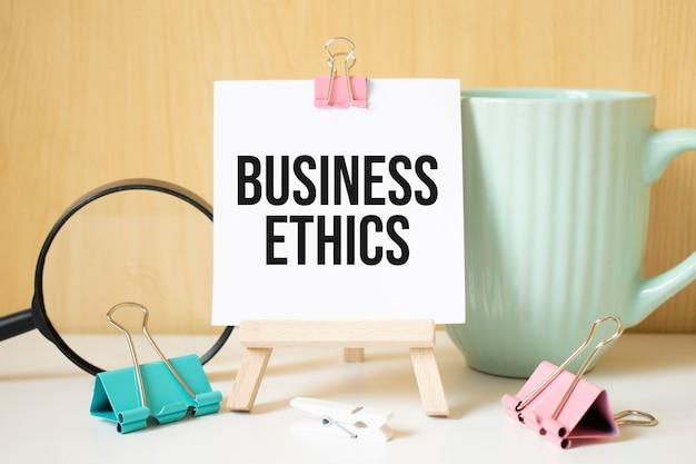 Tekst etyki biznesowej napisany na czarnym notatniku z lupą i piórem. koncepcja biznesu i osiągnięć.