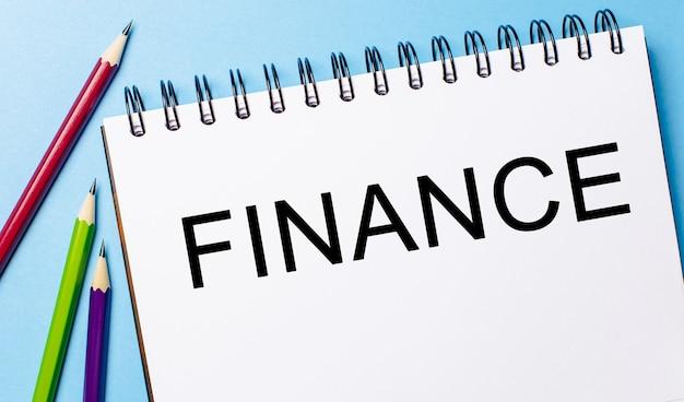Tekst finance na białym notatniku z ołówkami na niebieskiej ścianie