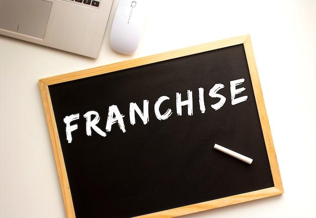 Tekst franchise napisany kredą na tablicy łupkowej. biurko. pomysł na biznes.