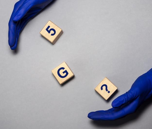 Tekst g na drewnianych kostkach i dłoniach w niebieskich rękawiczkach ochronnych na szarym stole g i koncepcja covid