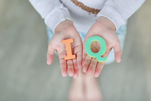 Tekst gąbki iq (iloraz inteligencji) na rękach dziecka