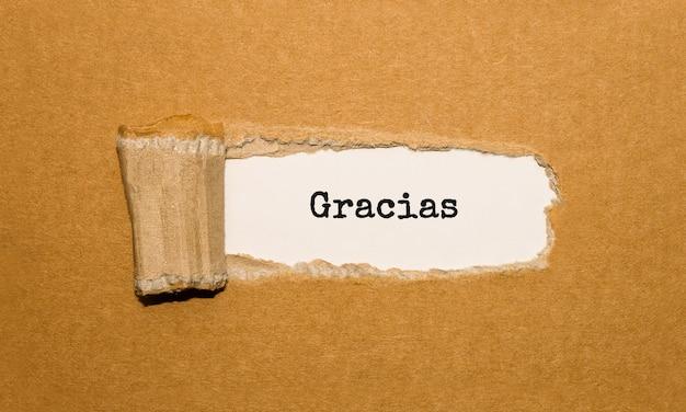 Tekst gracias pojawiający się za podartym brązowym papierem, zdjęcie stockowe