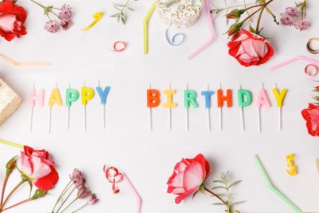 Tekst happy birthday literami z akcesoriami urodzinowymi, różą, świecami i konfetti na białym szarym tle