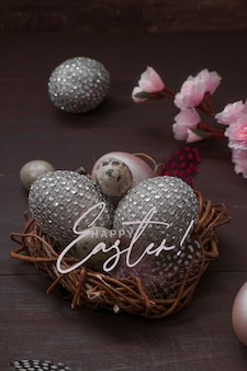 Tekst happy easter gniazdo z jajkami na drewnianym tle. wesołych świąt wielkanocnych kartkę z życzeniami z kreatywnymi pisankami i kwiat wiśni