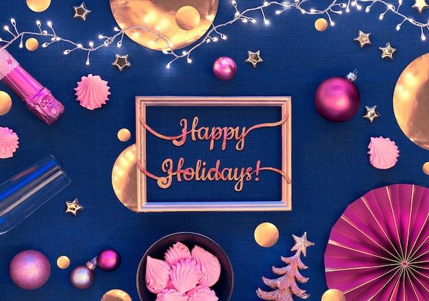 Tekst happy holiday w pozłacanej ramie. kartka świąteczna ze złotymi i różowymi dekoracjami, winoroślą i słodyczami