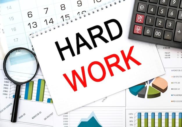 Tekst hard work na stołach finansowych z lupą. koncepcja biznesowa i finansowa. kalkulator, lupa i papier roboczy ze schematem.