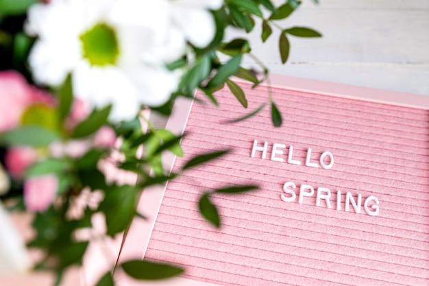 Tekst hello spring na różowej tablicy z pięknymi kwitnącymi kwiatami, kompozycja w stylu minimalizmu, miejsce na tekst.