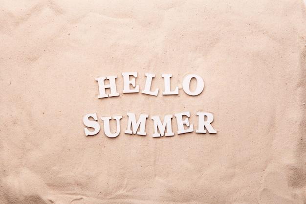 Tekst hello summer z białych liter na piasku. koncepcja czasu letniego.