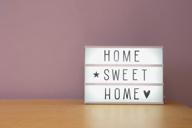 """Tekst """"home sweet home"""" w lighbox na drewnianej półce, nowoczesna dekoracja retro"""