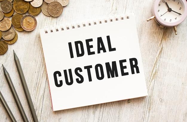 Tekst ideal customer na kartce notatnika. monety rozrzucone, ołówki na szarym tle drewnianych. koncepcja finansowa.