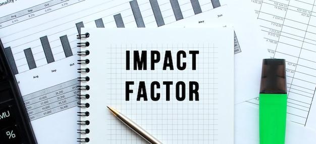 Tekst impact factor na stronie notatnika leżącego na wykresach finansowych na biurku. w pobliżu kalkulatora. pomysł na biznes.