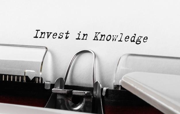 Tekst invest in knowledge wpisany na retro maszynie do pisania;