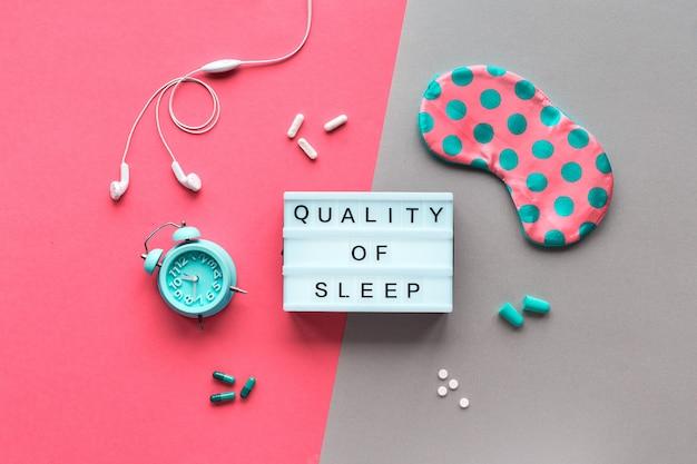 """Tekst """"jakość snu"""", koncepcja kreatywna. maska do spania w groszki, mały budzik, słuchawki i zatyczki do uszu, kapsułki ze środkiem nasennym. leżał płasko, dwukolorowy różowy zielony."""