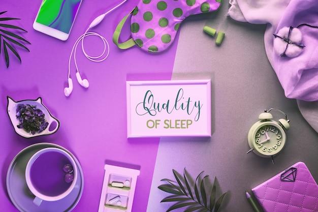 """Tekst """"jakość snu"""" w ramce. koncepcja kreatywnego zdrowego snu. maska do spania, budzik, słuchawki, zatyczki do uszu, herbata i pigułki."""