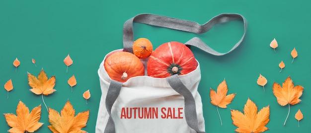 """Tekst """"jesienna wyprzedaż"""" na płóciennej torbie z pomarańczowymi dyniami, widok z góry. jesienne mieszkanie leżało na zielonym papierze, panoramiczna kompozycja. projekt transparentu jesień w kolorze zielonym i pomarańczowym."""
