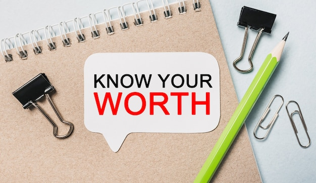 Tekst know your worth na białej naklejce z tłem biurowym. mieszkanie leżało na koncepcji biznesu, finansów i rozwoju