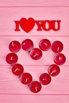 Tekst kocham cię i świece. serce z czerwonych podgrzewaczy i ozdobny napis i love you, widok z góry. pomysły na powitanie z walentynki.