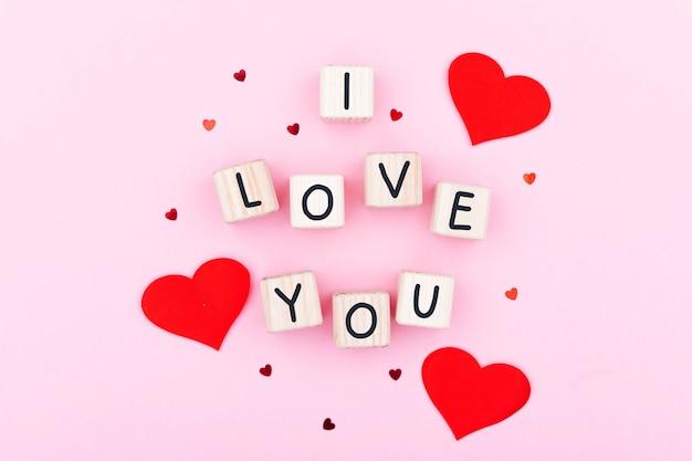Tekst kocham cię na drewnianym klocku. kartki okolicznościowe na różowym tle, kartka ozdobiona wzorem czerwonych serc, walentynki