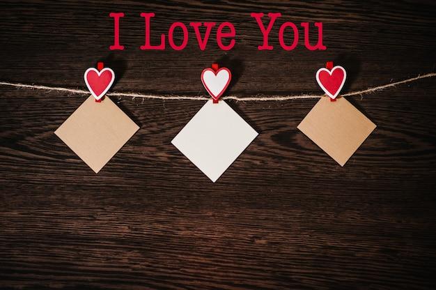 Tekst kocham cię. papier kraft, trzy puste, z czerwonym sercem zawieszonym na linie