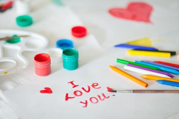 Tekst kocham cię rysowanie kolorowymi farbami na papierze. pędzle, farby, gwasz na stole.
